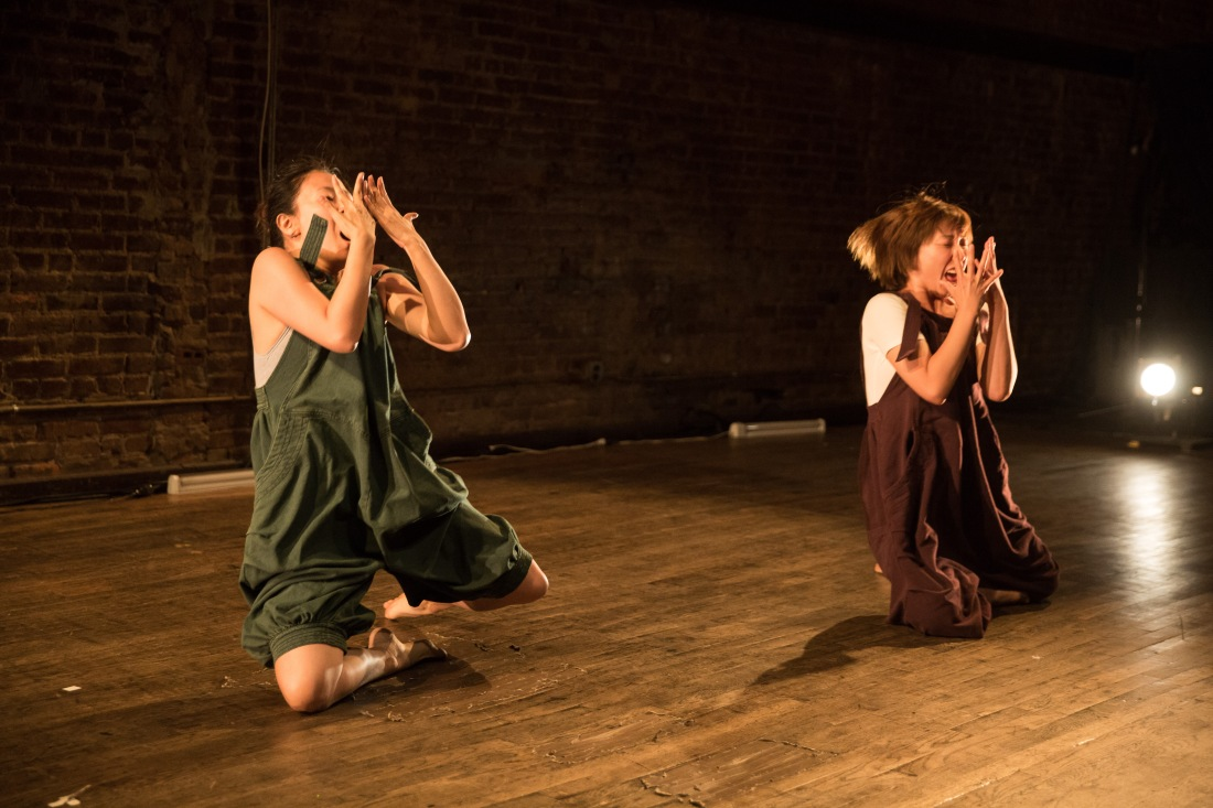 Two performers kneeling with their hands folded over their faces.